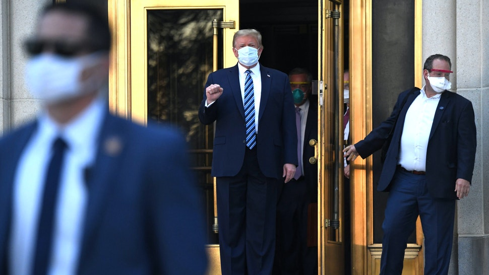 US President Donald Trump pumps his fist as he walks out of Walter Reed Medical Center in Bethesda, Maryland walking to Marine One on October 5, 2020, to return to the White House after being discharged.