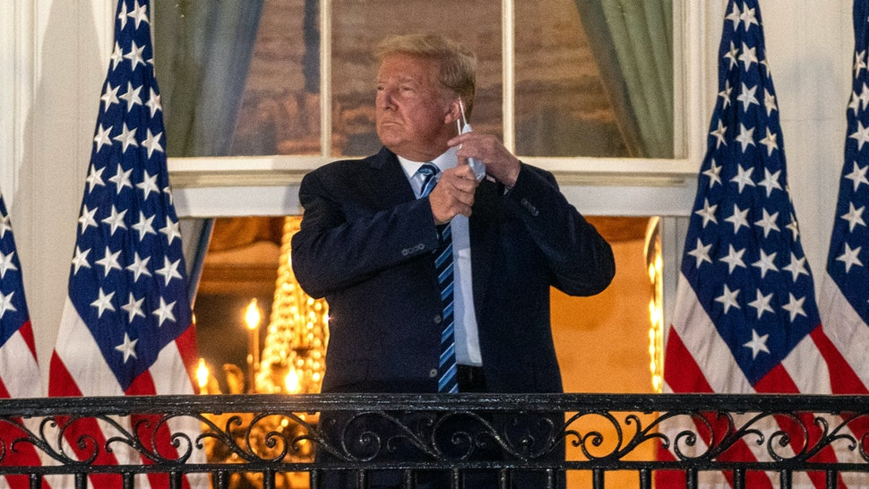 U.S. President Donald Trump removes his protective mask on the Truman Balcony of the White House in Washington, D.C., U.S., on Monday, Oct. 5, 2020. Trump's aides will try to keep him confined to the White House residence after being discharged from the hospital with Covid-19 but are unsure they can limit his movements.