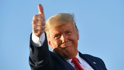 "US President Donald Trump gives a thumbs up as he leaves a rally at Tucson International Airport in Tucson, Arizona on October 19, 2020. - US President Donald Trump went after top government scientist Anthony Fauci in a call with campaign staffers on October 19, 2020, suggesting the hugely respected and popular doctor was an ""idiot."""