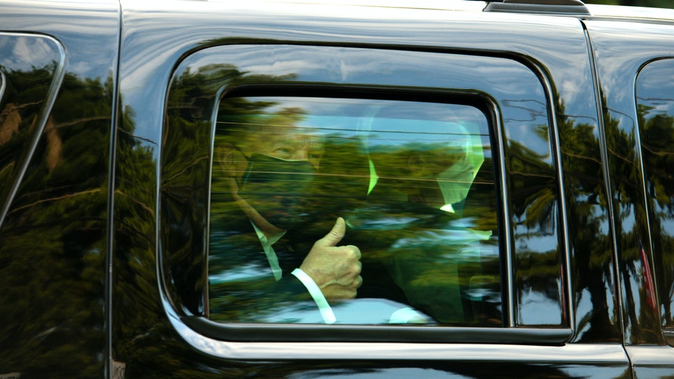 U.S. President Donald Trump wears a protective mask while giving a thumbs up as he is driven in a motorcade past supporters outside of Walter Reed National Military Medical Center in Bethesda, Maryland, U.S., on Sunday, Oct. 4, 2020. Trump briefly left his hospital in a car to greet supporters gathered outside, after posting a video on Twitter saying he was about to make a surprise visit.