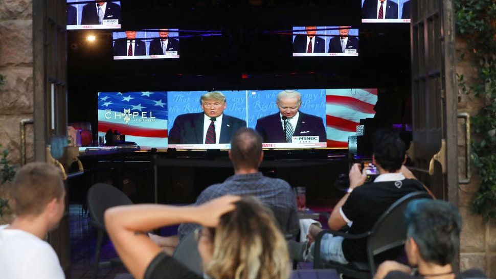 People sit and watch a broadcast of the first debate between President Donald Trump and Democratic presidential nominee Joe Biden at The Abbey, with socially distanced outdoor seating, on September 29, 2020 in West Hollywood, California. The debate being held in Cleveland, Ohio is the first of three scheduled debates between Trump and Biden. (Photo by Mario Tama/Getty Images)