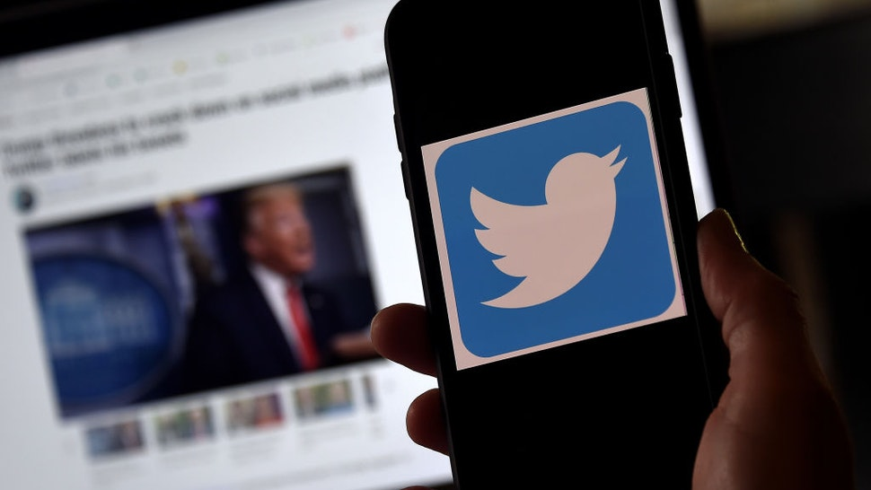 """In this photo illustration, a Twitter logo is displayed on a mobile phone with President Trump's Twitter page shown in the background on May 27, 2020, in Arlington, Virginia. - US President Donald Trump threatened Wednesday to shutter social media platforms after Twitter for the first time acted against his false tweets, prompting the enraged Republican to double down on unsubstantiated claims and conspiracy theories. Twitter tagged two of Trump's tweets in which he claimed that more mail-in voting would lead to what he called a """"Rigged Election"""" this November. (Photo by Olivier DOULIERY / AFP) (Photo by OLIVIER DOULIERY/AFP via Getty Images)"""