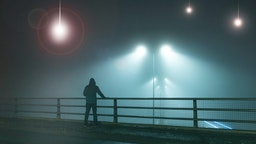 A hooded figure, standing with back to camera on a bridge, looking at UFO alien spaceships coming downfrom the sk., Street lights. On a foggy night.