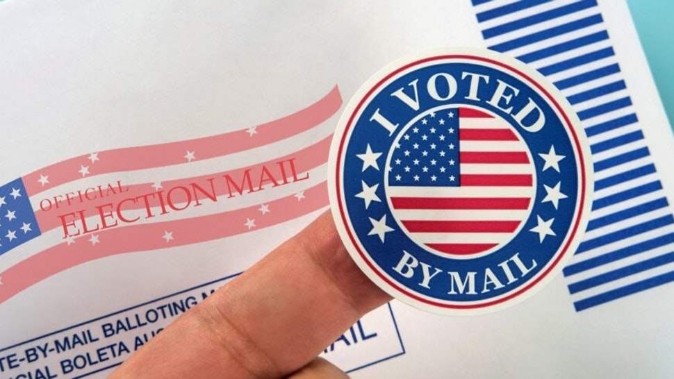 Human finger holding sticker above voting mail