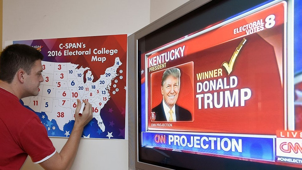 TOPSHOT - Jake Krupa colors in an electoral map as states are projected for Republican presidential candidate Donald Trump or Democratic Presidential candidate Hillary Clinton at an election watching party in Coconut Grove, Florida, on November 8, 2016. / AFP / RHONA WISE (Photo credit should read