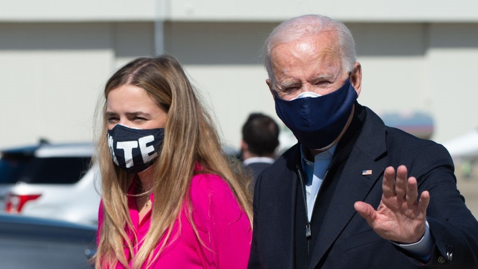 Democratic presidential nominee and former Vice President Joe Biden stands next to his granddaughter Finnegan after landing at the Raleigh-Durham International Airport on October 18, 2020 in Durham, North Carolina. - President Donald Trump and rival Joe Biden hit the ground Sunday in the swing states that will decide the US election, as the campaign turns increasingly vicious 16 days before voting. Trump, scrambling to make up lost ground, is on a furious multi-state barnstorming tour hopping from Nevada to California and then back to Nevada for a day of rallies and fundraising. (Photo by ROBERTO SCHMIDT / AFP) (Photo by