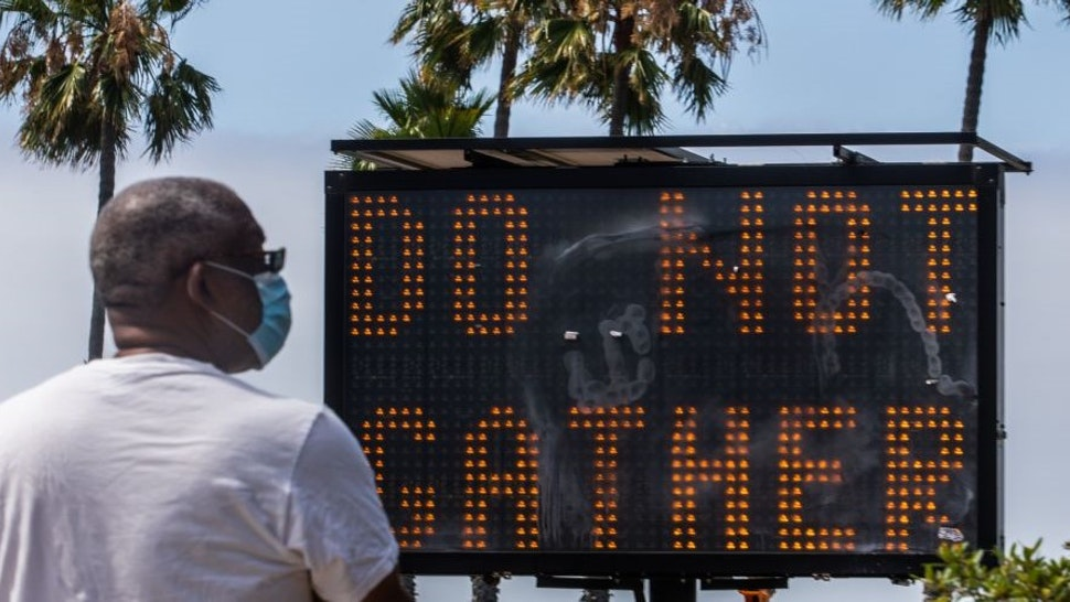 A man wearing a facemask checks his phone near a sign urging people not to gather, while he walks on the beach in Long Beach, California, on July 14, 2020. - California's Governor Gavin Newsom announced a significant rollback of the state's reopening plan on July 13, 2020 as coronavirus cases soared across America's richest and most populous state. (Photo by Apu GOMES / AFP) (Photo by
