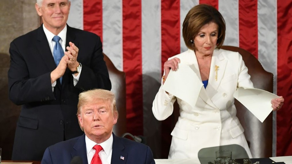 TOPSHOT - US Vice President Mike Pence claps as Speaker of the US House of Representatives Nancy Pelosi appears to rip a copy of US President Donald Trumps speech after he delivers the State of the Union address at the US Capitol in Washington, DC, on February 4, 2020. (Photo by MANDEL NGAN / AFP) (Photo by