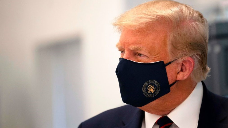 TOPSHOT - US President Donald Trump wears a mask as he tours a lab where they are making components for a potential vaccine at the Bioprocess Innovation Center at Fujifilm Diosynth Biotechnologies in Morrisville, North Carolina on July 27, 2020. (Photo by JIM WATSON / AFP) (Photo by