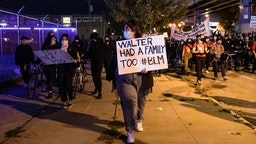 Protesters march through West Philadelphia on October 27, 2020, to protest the fatal shooting of 27-year-old Walter Wallace, a Black man, by police. - Hundreds of people demonstrated in Philadelphia late on October 27, with looting and violence breaking out in a second night of unrest after the latest police shooting of a Black man in the US. The fresh unrest came a day after the death of 27-year-old Walter Wallace, whose family said he suffered mental health issues. On Monday night hundreds of demonstrators took to the streets, with riot police pushing them back with shields and batons. (Photo by GABRIELLA AUDI / AFP) (Photo by
