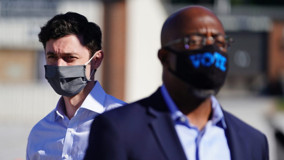 Democratic U.S. Senate candidates Jon Ossoff and Rev. Raphael Warnock are seen at a campaign event on October 3, 2020 in Lithonia, Georgia.