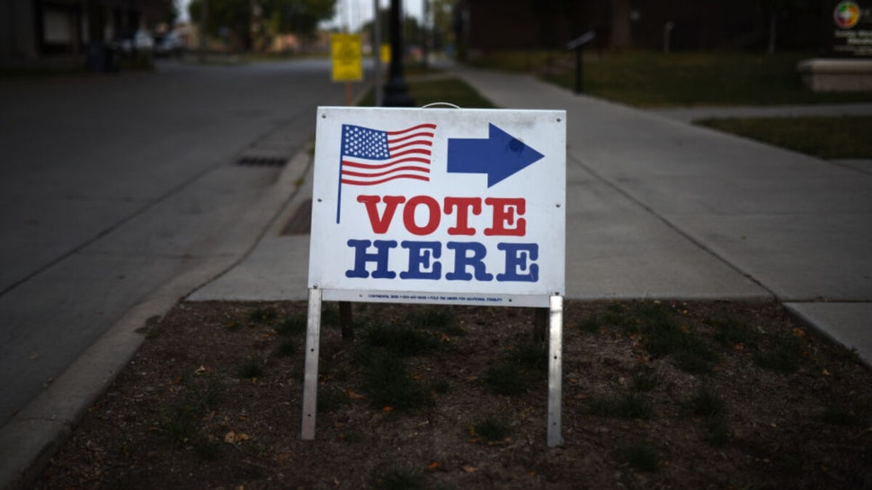 """A sign reading """"Vote Here"""" points toward a polling place for the 2018 Minnesota primary election at Holy Trinity Lutheran Church on August 14, 2018 in Minneapolis, Minnesota."""
