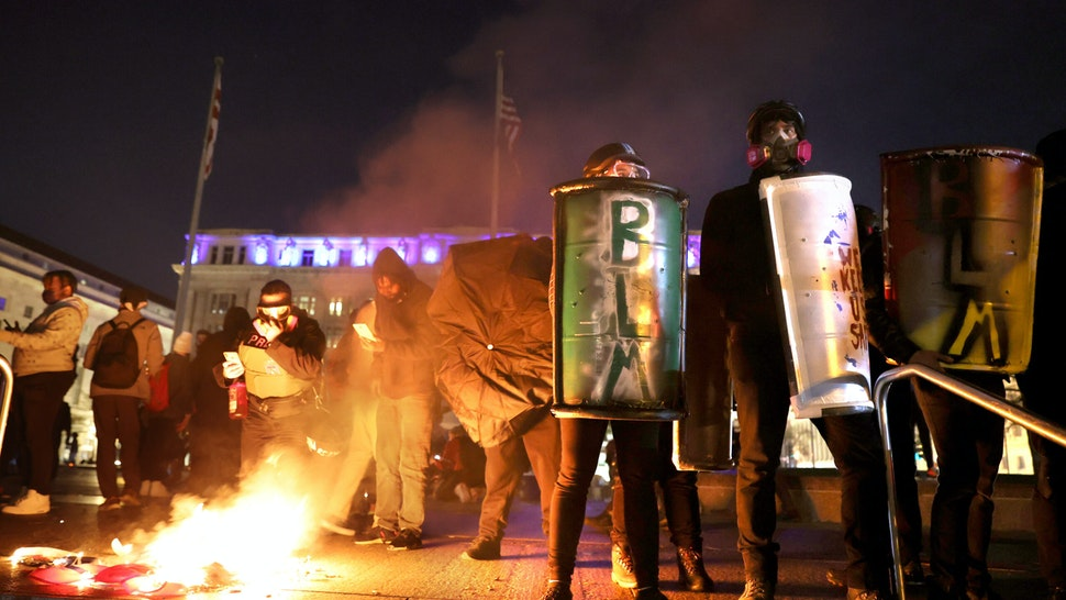"""WASHINGTON, DC - NOVEMBER 14: Black Lives Matter protesters hold shields as they stand next to a small fire during a protest following the """"Million MAGA March"""" from Freedom Plaza to the Supreme Court, on November 14, 2020 in Washington, DC. Supporters of U.S. President Donald Trump gathered to protest the outcome of the 2020 presidential election. (Photo by Tasos Katopodis/Getty Images)"""