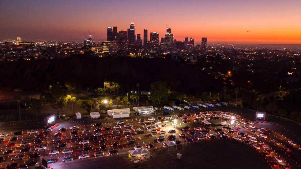 This aerial view shows cars lined up at the Dodger Stadium parking lot for Covid-19 testing with the downtown Los Angeles skyline in the distance, in Los Angeles, California, on November 14, 2020.