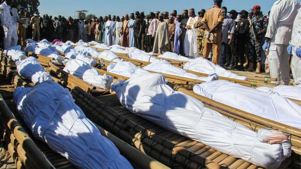 TOPSHOT - Mourners attend the funeral of 43 farm workers in Zabarmari, about 20km from Maiduguri, Nigeria, on November 29, 2020 after they were killed by Boko Haram fighters in rice fields near the village of Koshobe on November 28, 2020. - The assailants tied up the agricultural workers and slit their throats in the village of Koshobe. The victims were labourers from Sokoto state in northwest Nigeria, roughly 1,000 kilometres (600 miles) away, who had travelled to the northeast to find work.