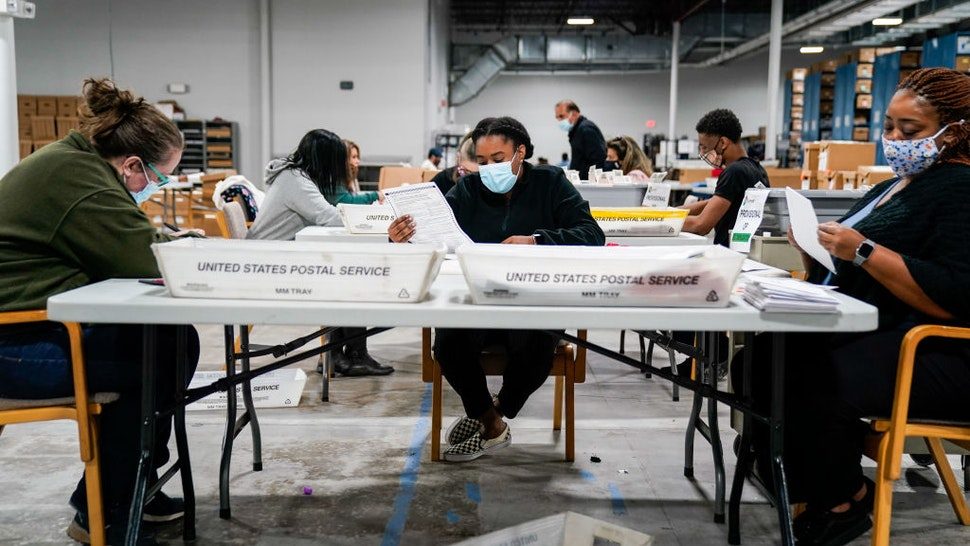 LAWRENCEVILLE, GA - NOVEMBER 06: Election workers validate ballots at the Gwinnete County Elections Office on Friday, Nov. 6, 2020 in Lawrenceville, GA. With the surge in vote by mail/absentee ballots, analysts cautioned it could take days to count all the ballots, leading some states to initially look like victories for President Trump only to later shift towards democratic Presidential candidate Joe Biden. (Kent Nishimura / Los Angeles Times via Getty Images)