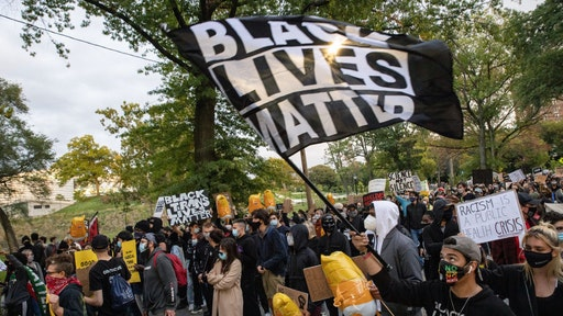 CLEVELAND, OHIO, UNITED STATES - 2020/09/29: Protesters wearing masks march through University Circle while holding up placards and banners during the protest.