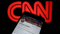 Donald Trump's Twitter timeline is seen on a smartphone against a backdrop with the CNN TV channel logo, in Ankara, Turkey on December 9, 2018.