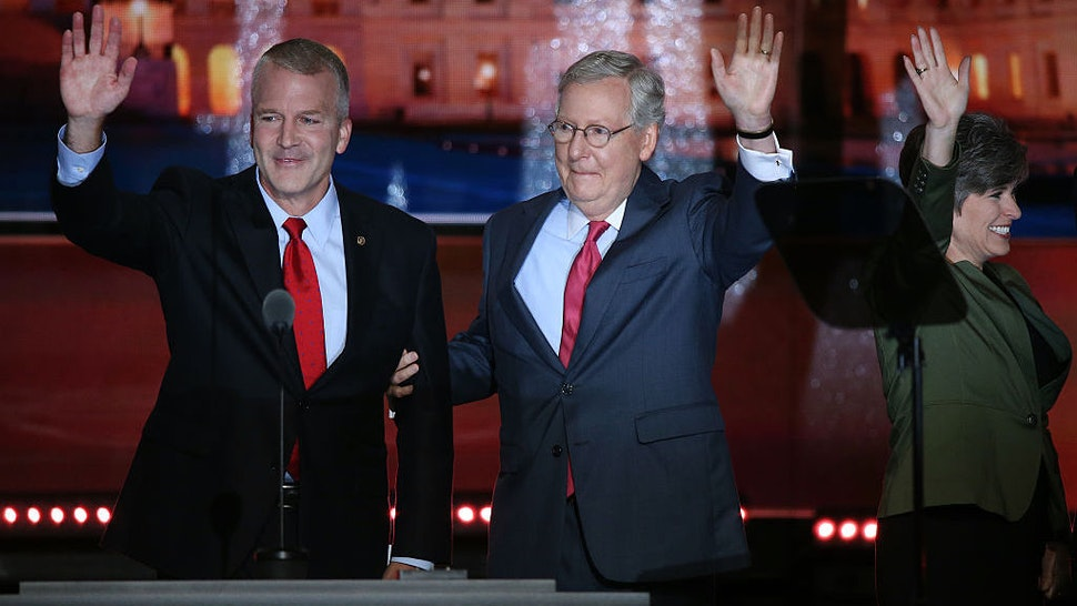 Senator Dan Sullivan, a Republican from Alaska, from left, waves on stage with Senate Majority Leader Mitch McConnell, a Republican from Kentucky, and Senator Joni Ernst, a Republican from Iowa, during the Republican National Convention (RNC) in Cleveland, Ohio, U.S., on Tuesday, July 19, 2016. Donald Trump sought to use a speech by his wife to move beyond delegate discontent at the Republican National Convention, only to have the second day open with an onslaught of accusations that his wife's speech lifted phrases from one delivered by Michelle Obama in 2008. Photographer: John Taggart/Bloomberg