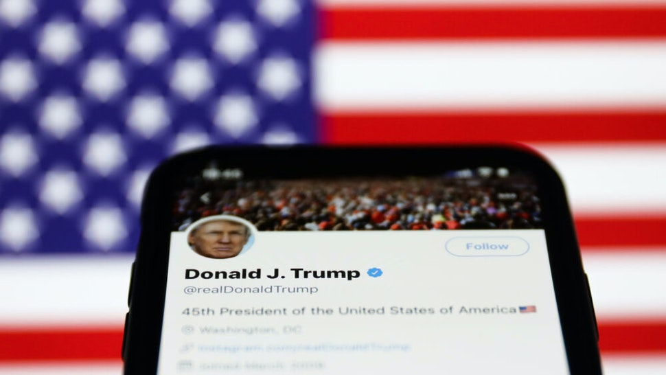 Twitter feed of the President of the USA Donald Trump is seen displayed on a phone screen with American flag in the background in this illustration photo taken on October 18, 2020. (Photo Illustration by Jakub Porzycki/NurPhoto via Getty Images)