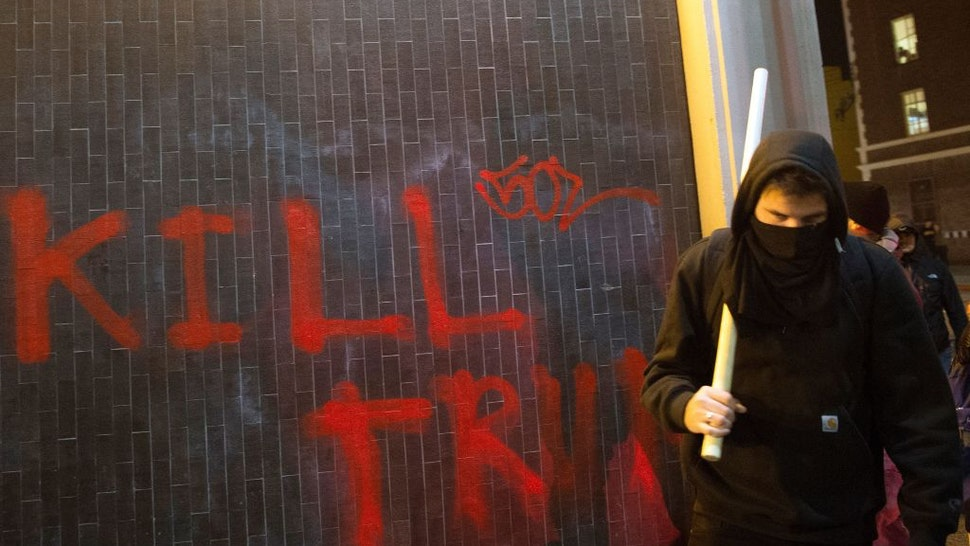 A protester walks with a pipe near graffiti in Berkeley, California on February 1, 2017. - Violent protests erupted on February 1 at the University of California at Berkeley over the scheduled appearance of a controversial editor of the conservative news website Breitbart. (Photo by Josh Edelson / AFP) (Photo by JOSH EDELSON/AFP via Getty Images)