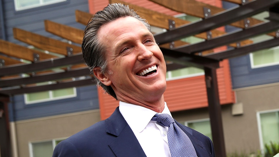 SAN FRANCISCO, CA - AUGUST 22: California Lt. Gov. and California gubernatorial candidate Gavin Newsom (L) laughs with a resident as he visits the Alice Griffith Apartments on August 22, 2018 in San Francisco, California. Lt. Gov. Gavin Newsom and San Francisco mayor London Breed toured a low-income housing complex. Newsom leads Republican gubernatorial candidate John Cox by an average of 23 percentage points in recent polls.