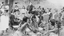A depiction of early settlers of the Plymouth Colony sharing a harvest Thanksgiving meal with members of the local Wampanoag tribe at the Plymouth Plantation, Plymouth, Massachusetts, 1621.