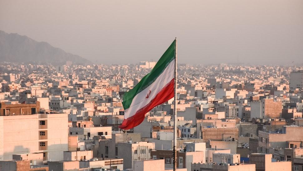Iranian flag waving with city skyline on background in Tehran, Iran - stock photo