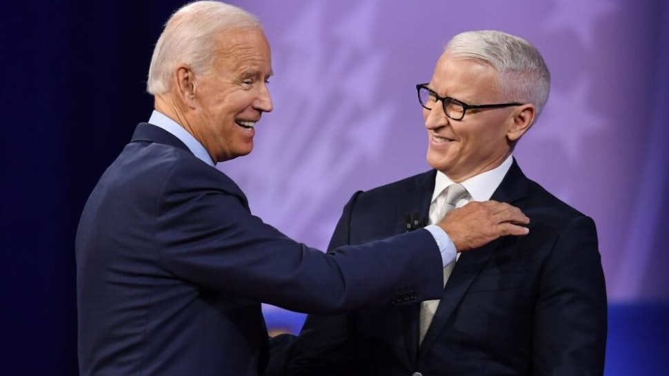 Democratic presidential hopeful former US Vice President Joe Biden (L) laughs with moderator CNN's Anderson Cooper during a town hall devoted to LGBTQ issues hosted by CNN and the Human rights Campaign Foundation at The Novo in Los Angeles on October 10, 2019.