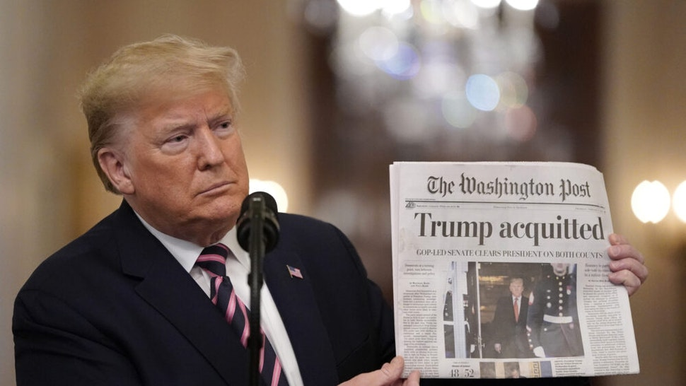 WASHINGTON, DC - FEBRUARY 06: U.S. President Donald Trump holds a copy of The Washington Post as he speaks in the East Room of the White House one day after the U.S. Senate acquitted on two articles of impeachment, ion February 6, 2020 in Washington, DC. After five months of congressional hearings and investigations about President Trump's dealings with Ukraine, the U.S. Senate formally acquitted the president on Wednesday of charges that he abused his power and obstructed Congress.