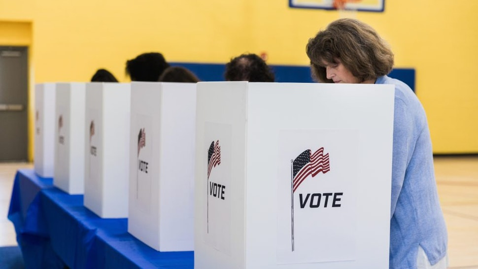 A photo with a diminishing perspective of multi-ethnic people voting at the voting booths.