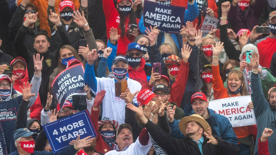 Supporters strain to catch a Make America Great Again hat thrown by President Donald Trump during a rally on October 26, 2020 in Lititz, Pennsylvania.