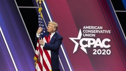 U.S. President Donald Trump hugs and kisses the American flag during the Conservative Political Action Conference (CPAC) in National Harbor, Maryland, U.S., on Saturday, Feb. 29, 2020.