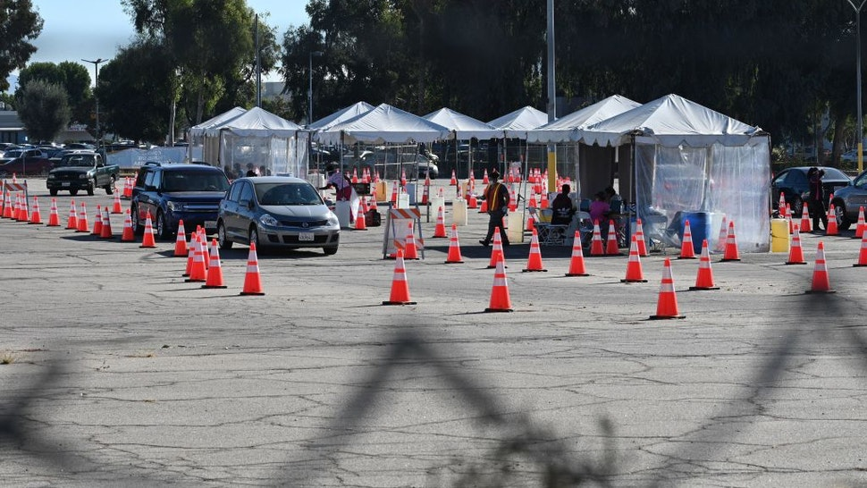 COVID-19 testing site staff directs traffic at a drive-up testing site in Los Angeles, California, November 17, 2020.