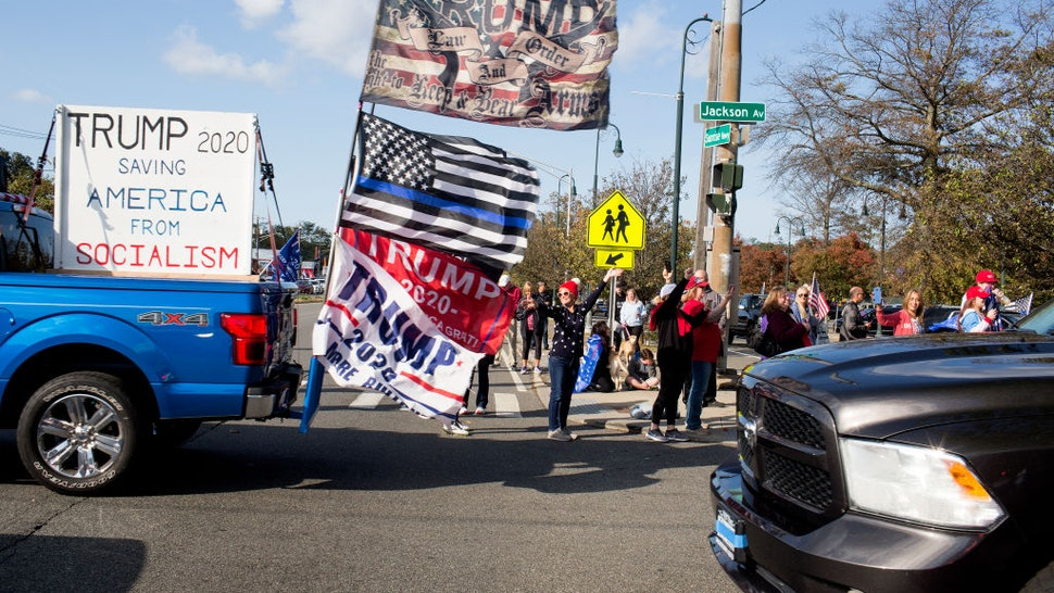 Trump supporters gather in a Long Island Rail Road parking lot before driving in cars as part of a caravan on October 18, 2020 in Seaford, New York.