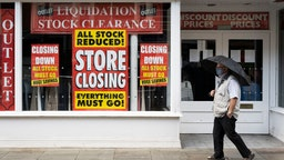 A man wearing a face mask walks past a shop with signs in the window saying its closing down in Newport town centre on October 31, 2020 in Newport, Wales.