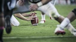 American football players readying to kick ball. - stock photo