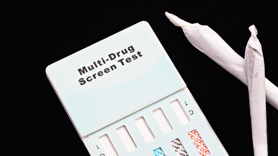 A multi-drug urine testing kit, designed for use at home, sits next to two hand-rolled marijuana cigarettes.