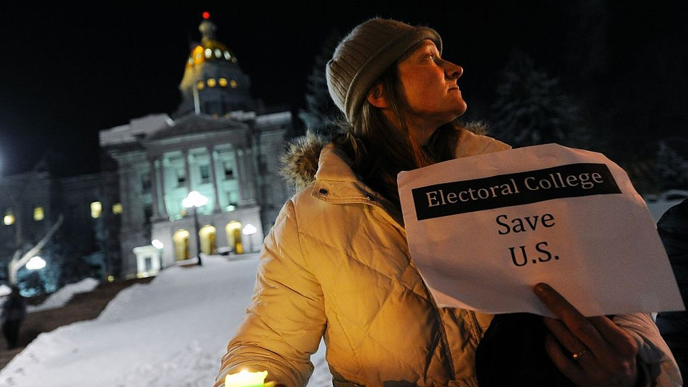 """Ruth Fulton, 44, demonstrates during a candlelight vigil against US President-elect Donald Trump outside the Colorado Capitol building on the eve of the Electoral College vote, in Denver, Colorado on December 18, 2016. """"The Electoral College is supposed to be a safeguard against exactly this sort of person,"""" said Fulton. / AFP / Chris Schneider (Photo credit should read CHRIS SCHNEIDER/AFP via Getty Images)"""