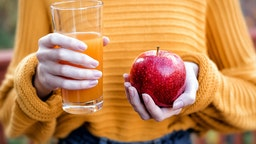 Young woman holding glass of apple juice and fresh apple - stock photo