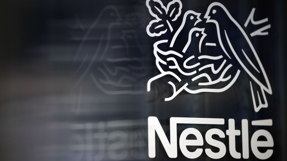 A Nestle birds nest logo is displayed on a glass door ahead of a news conference announcing the company's full year results in Vevey, Switzerland, on Thursday, Feb. 15, 2018.