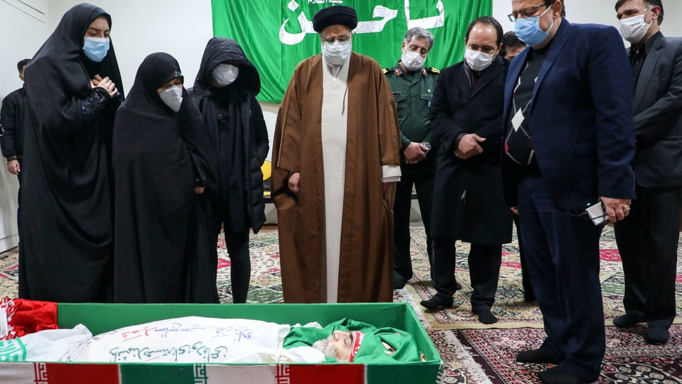 "Iran's Judiciary Chief Ayatollah Ebrahim Raisi (C) pays respects to the body of slain scientist Mohsen Fakhrizadeh among his family, in the capital Tehran on November 28, 2020. - Mohsen Fakhrizadeh, dubbed by Israel as the ""father"" of Iran's nuclear programme, died on November 27 after being seriously wounded when assailants targeted his car and engaged in a gunfight with his bodyguards outside Tehran, according to Iran's defence ministry. The assassination comes less than two months before US President-elect Joe Biden is due to take office, after a tumultuous four years of hawkish foreign policy in the Middle East under President Donald Trump."
