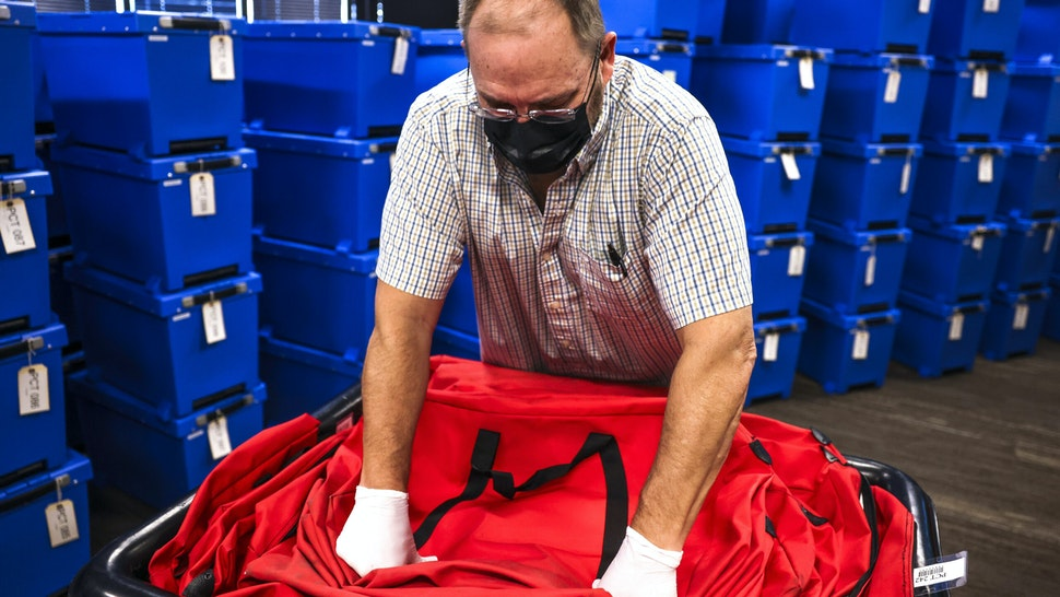 CHARLOTTE, NC - NOVEMBER 04: An elections specialist packs up bags in a room filled with counted ballots the day after the election at the Mecklenburg County Board of Elections office on November 4, 2020 in Charlotte, North Carolina. The presidential race in North Carolina was too close to call on election night as mail-in ballots are still coming in across the state.