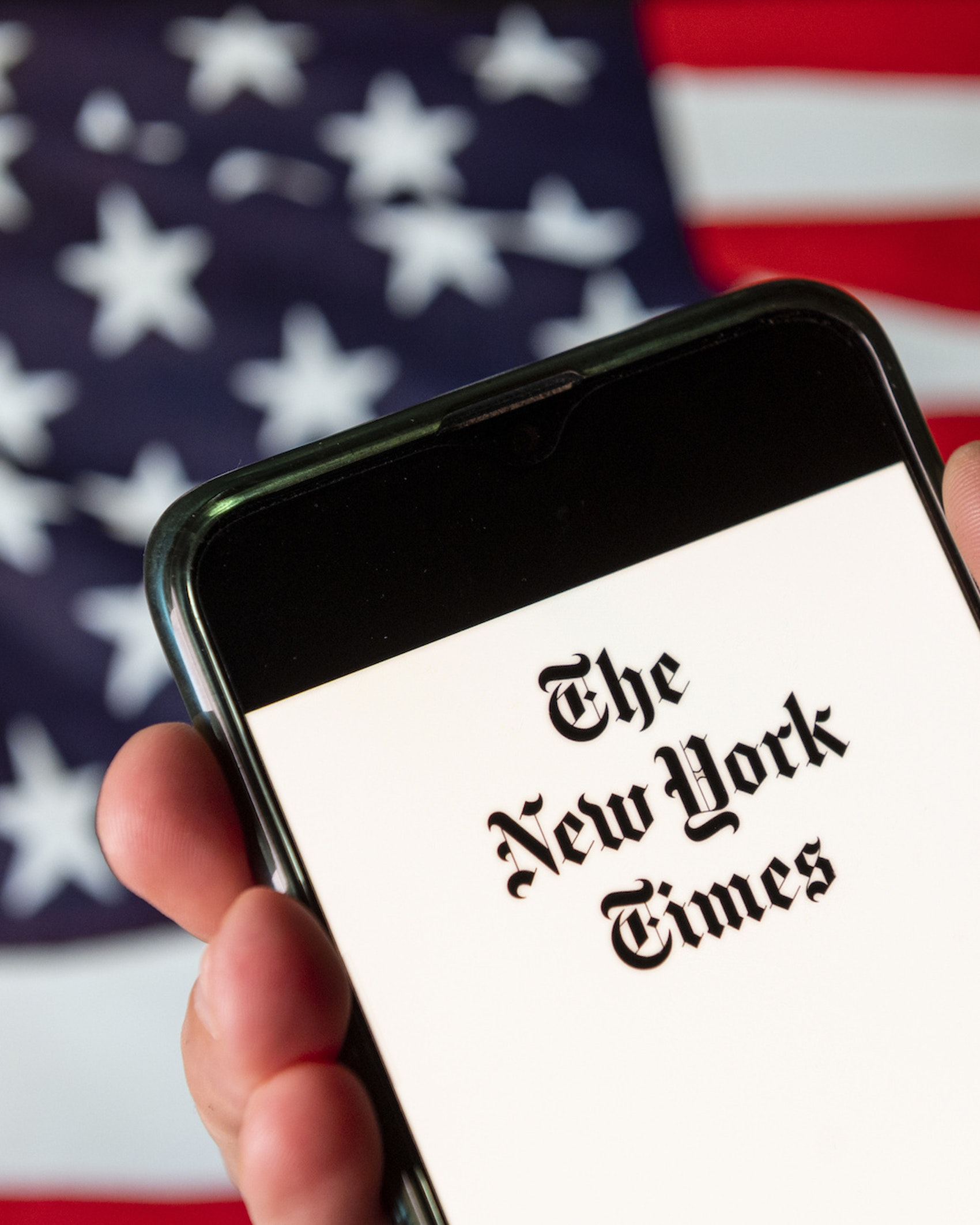 In this photo illustration the American newspaper The New York Times (NYT) logo is seen on an Android mobile device with United States of America flag in the background. (Photo Illustration by Budrul Chukrut/SOPA Images/LightRocket via Getty Images)