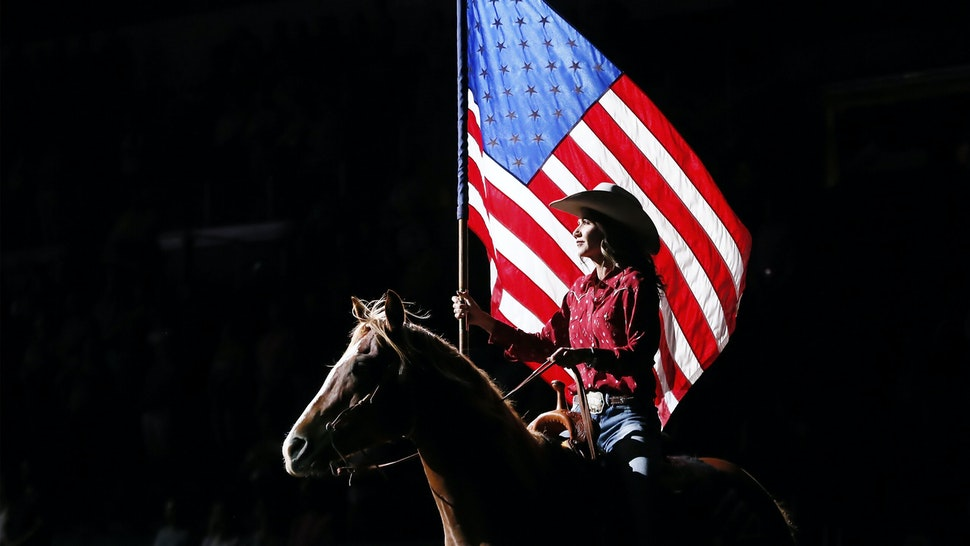 SIOUX FALLS, SD - JULY 11: South Dakota's Governor Kristi Noem holds the U.S flag riding a horse during the Monster Energy Team Challenge, on July 11, 2020, at the Denny Sanford PREMIER Center, Sioux Falls, SD.