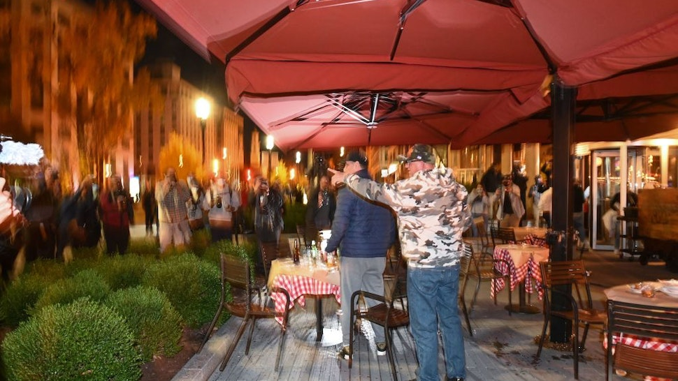 Trump supporters react as a crowd closes in on them at the terrace of a restaurant near Black Lives Matter Plaza in Washington, DC on November 14, 2020.