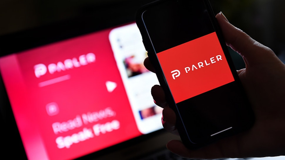 """This illustration picture shows social media application logo from Parler displayed on a smartphone with its website in the background in Arlington, Virginia on July 2, 2020. - Amid rising turmoil in social media, recently formed social network Parler is gaining with prominent political conservatives who claim their voices are being silenced by Silicon Valley giants. Parler, founded in Nevada in 2018, bills itself as an alternative to """"ideological suppression"""" at other social networks."""