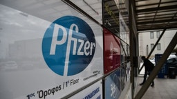 """A man entry at the building where Pfizer's office located in Thessaloniki on November 10, 2020. - Pfizer stock surged higher on November 9, 2020 prior to the opening of Wall Street trading after the company announced its vaccine is """"90 percent effective"""" against Covid-19 infections. The news cheered markets worldwide, especially as coronavirus cases are spiking, forcing millions of people back into lockdown. (Photo by Sakis MITROLIDIS / AFP) (Photo by SAKIS MITROLIDIS/AFP via Getty Images)"""