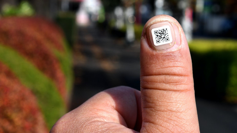 This picture taken on December 5, 2016 shows a city officer displaying a QR code on his fingernail near the Iruma city hall in Iruma, Saitama prefecture, a western suburb of Tokyo. A Japanese city has introduced a novel way to keep track of senior citizens with dementia who are prone to getting lost -- tagging their fingers and toes with scan-able barcodes. A company in Iruma, north of Tokyo, developed tiny nail stickers, each of which carries a unique identity number to help concerned families find missing loved ones, according to the city's social welfare office