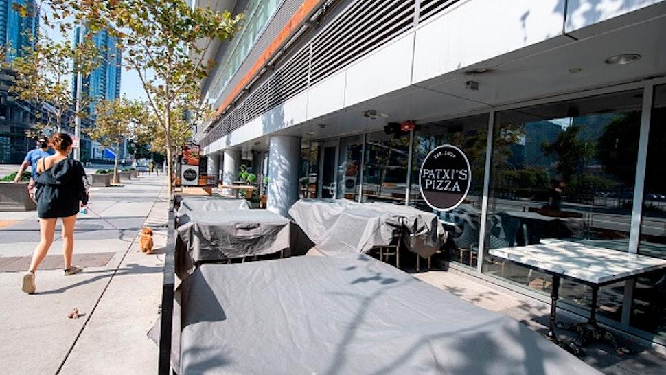 People walk by closed restaurants at LA Live amid the coronavirus Pandemic, September 18, 2020, in Los Angeles California.